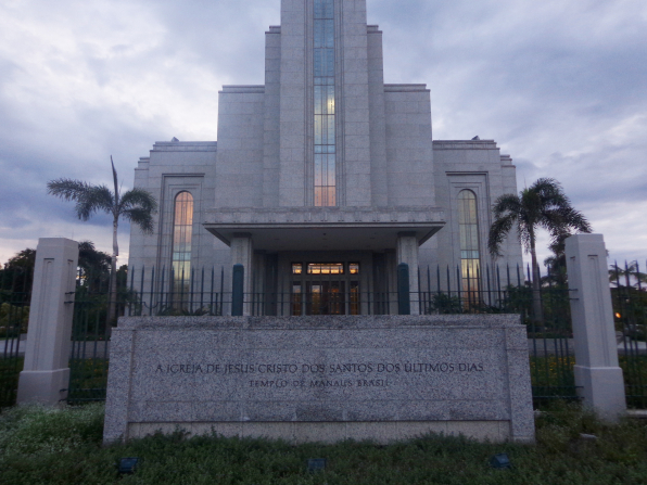 The name sign in front of the main entrance of the Manaus Brazil Temple at sunset, with the sunset reflecting in the windows.