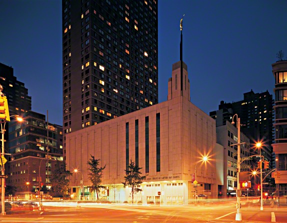 A view of the Manhattan New York Temple front entrance in the late evening, lit up by surrounding street lights, with buildings seen in the distance.