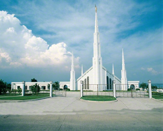 A view of the front gate entrance to the Manila Philippines Temple, with a blue sky and clouds in the distance.