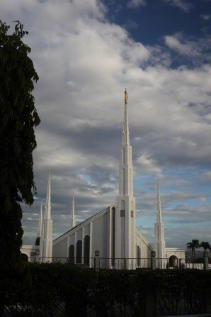 A distant view of the Manila Philippines Temple, with storm clouds behind.