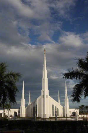 A distant view of the Manila Philippines Temple, with palm tree leaves shown on the sides and storm clouds in the distance.