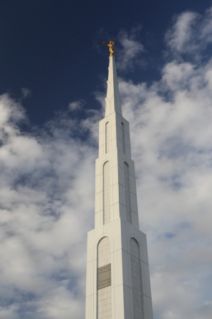 A view of the Manila Philippines Temple spire, with a blue sky and clouds in the distance.