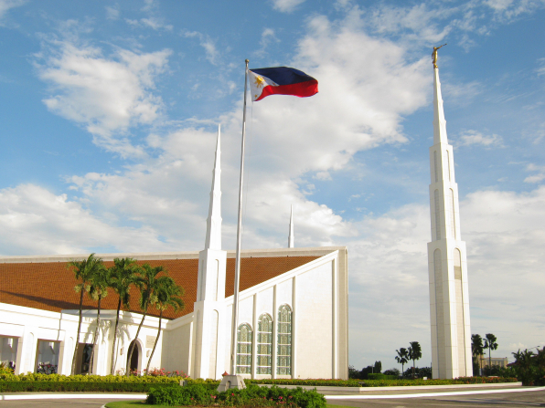 A view of the entrance and grounds to the Manila Philippines Temple, with a separated spire tower to the right and the Philippines flag blowing in the wind on a sunny day.