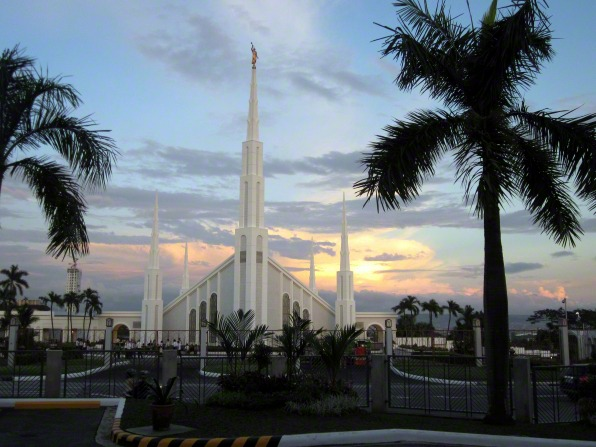 The entrance and grounds view of the Manila Philippines Temple, with palm trees surrounding and the late evening sky coloring the clouds.