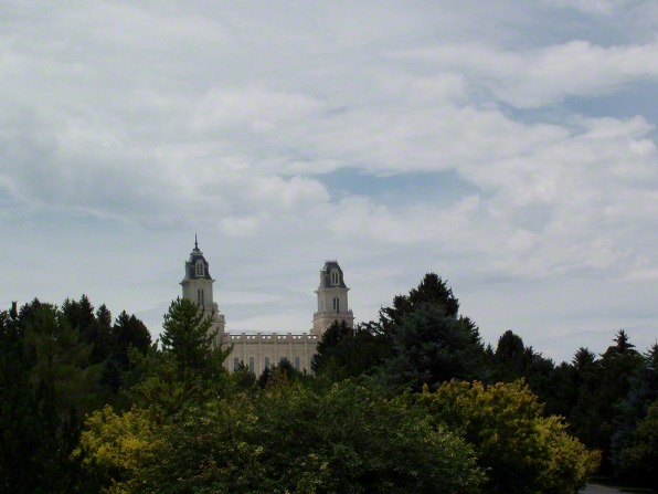 The spires of the Manti Utah Temple are visible from above the tree tops.