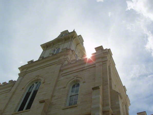 A worm's-eye view, looking up toward the sun shining past the spire of the Manti Utah Temple.