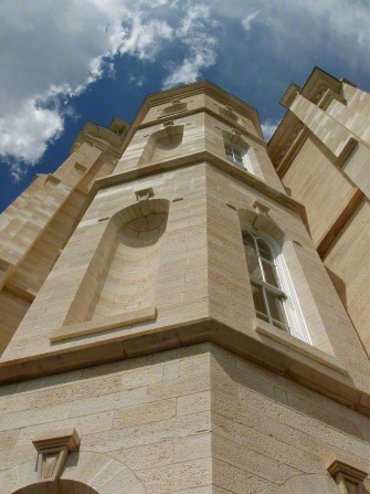 A low-angle view of part of the Manti Utah Temple exterior, including windows, with a blue sky and clouds beyond.