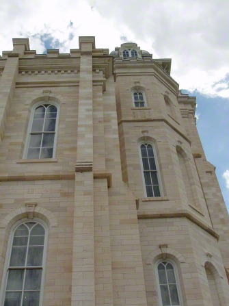 A low-angle view of one wall of windows on the Manti Utah Temple exterior.