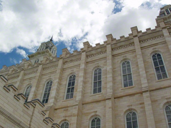 A close-up view of one side of the Manti Utah Temple exterior—walls, windows, and spire—with a blue sky and clouds above.