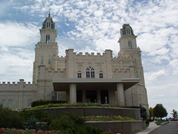 The front entrance of the Manti Utah Temple, with a view of the grounds and flowers and with clouds spotting a blue sky in the distance.