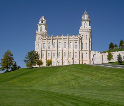 A side view of the Manti Utah Temple on top of a green grassy hill with trees surrounding.