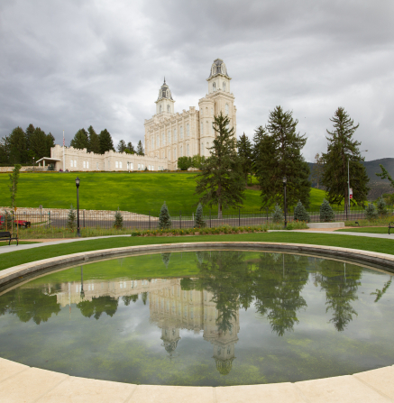 The Manti Utah Temple on a green hill with trees, seen reflected in the water of a pond on an overcast, rainy day.
