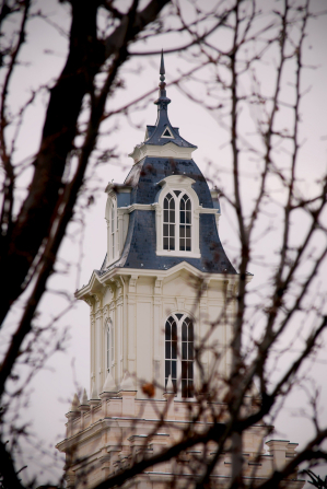 A spire from the Manti Utah Temple is seen through the branches of a tree.