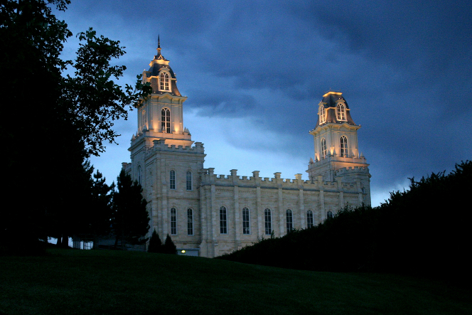 The Manti Utah Temple lit up in the late evening, behind silhouetted trees and bushes.