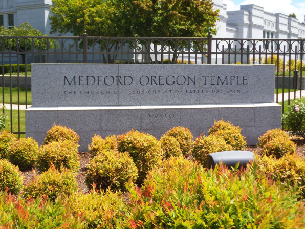 A close-up of the Medford Oregon Temple name sign in front of the temple, beyond the fence surrounding the grounds.