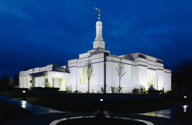 The exterior of the Medford Oregon Temple entrance is lit up in the dark evening.