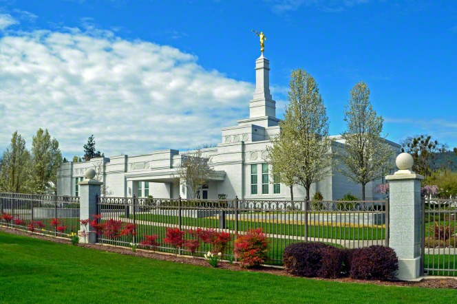 The Medford Oregon Temple exterior entrance and landscape are seen beyond a fence surrounding the grounds on a sunny day.