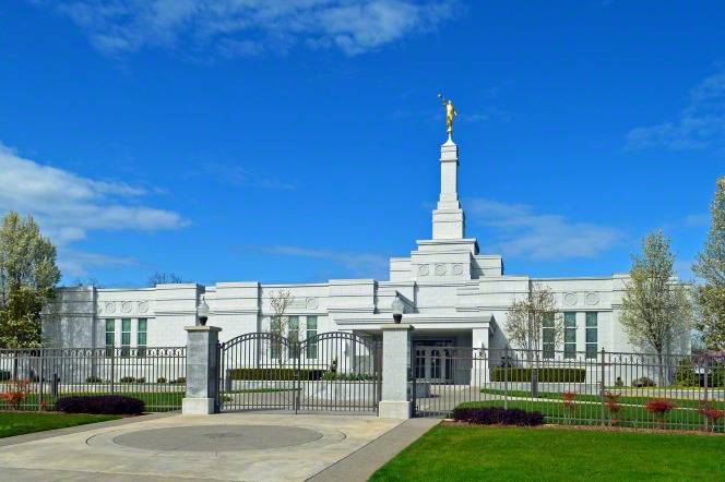 The front entrance to the Medford Oregon Temple, surrounded by a fence, with a blue sky above.