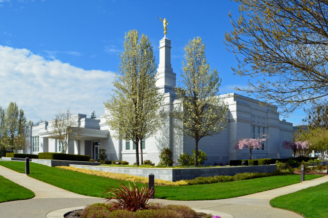 A side and front view of the Medford Oregon Temple, with a landscape of green grass and blossoming trees.