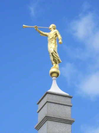 The angel Moroni statue on top of the Melbourne Australia Temple, with a blue sky behind.