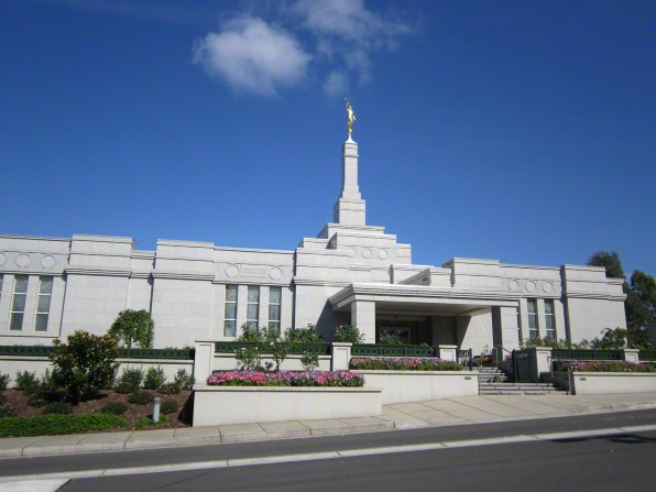A view of the Melbourne Australia Temple exterior entrance and grounds with flowers, seen from across the street on a sunny day.