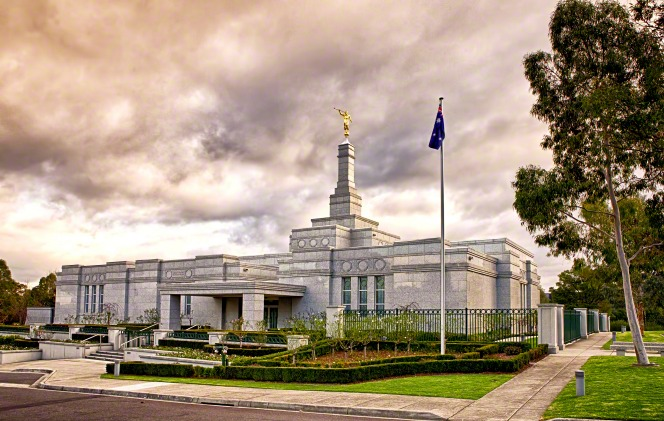 The front entrance of the Melbourne Australia Temple, with a flag and a stormy sky.
