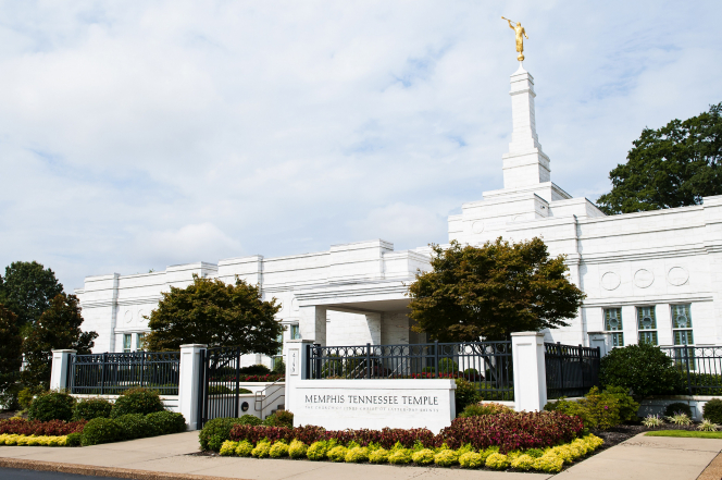 The Memphis Tennessee Temple sign surrounded by flowers, with the temple in the background and clouds overhead.
