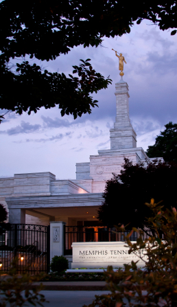 A portrait view of the Memphis Tennessee Temple in the evening, with the temple name sign lit up in front.