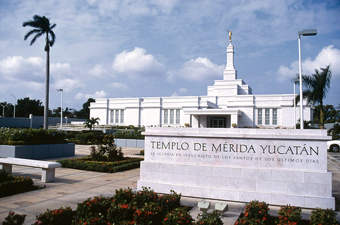 The Mérida Mexico Temple name sign up close, with the temple in the background.