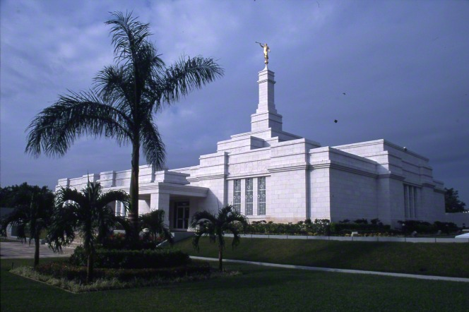 The Mérida Mexico Temple viewed at an angle, showing the side and front entrance, with some of the gardens of flowers and palm trees on an overcast day.