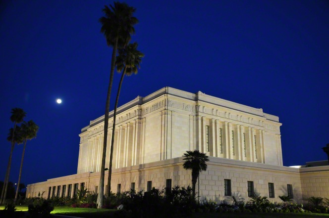 The Mesa Arizona Temple and palm trees lit up at night, with a dark blue sky and moon in the distance.