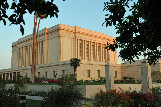 The Mesa Arizona Temple is viewed at an angle, with a landscape of grass and flowers and trees at sunset.