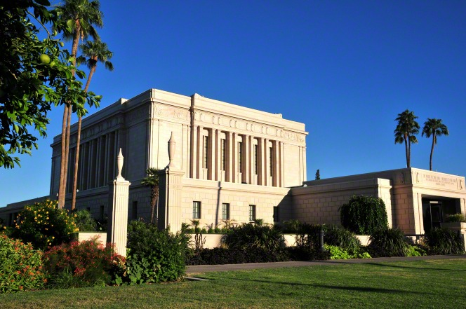 The entrance of the Mesa Arizona Temple is viewed from the side, with a surrounding landscape of plants and trees.
