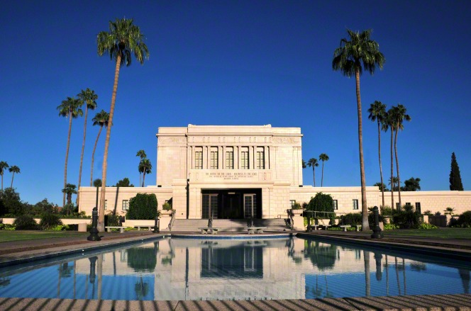 The Mesa Arizona Temple reflected in a pool on a sunny day, with surrounding palm trees and a blue sky.