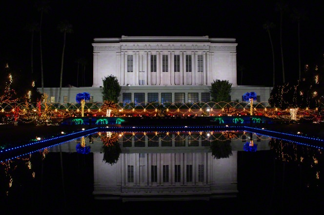The Mesa Arizona Temple is seen reflected in a pool of water, surrounded by Christmas lights at night.