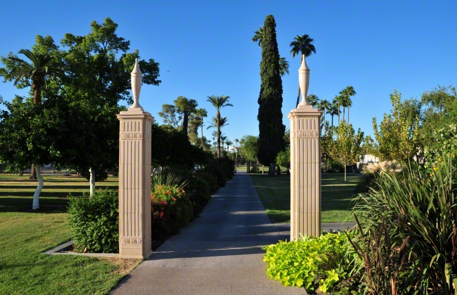 The Mesa Arizona Temple exterior gate entrance, with two pillars and a road lined with plants and trees.