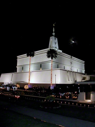 A front and side view of the Mexico City Mexico Temple at night, lit up with lights for the Christmas holiday, with a moon in the sky.