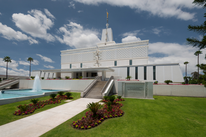 A front view of the Mexico City Mexico Temple in the daytime, with green lawns and a water feature in the foreground.