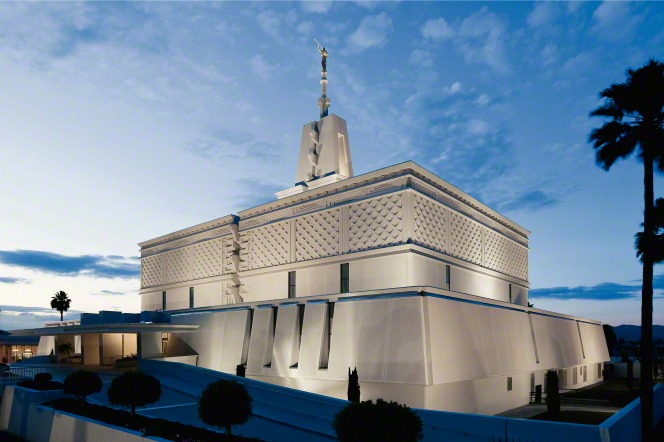 The exterior of the Mexico City Mexico Temple is lit up, viewed from the front entrance side in the evening, with a surrounding landscape of trees.