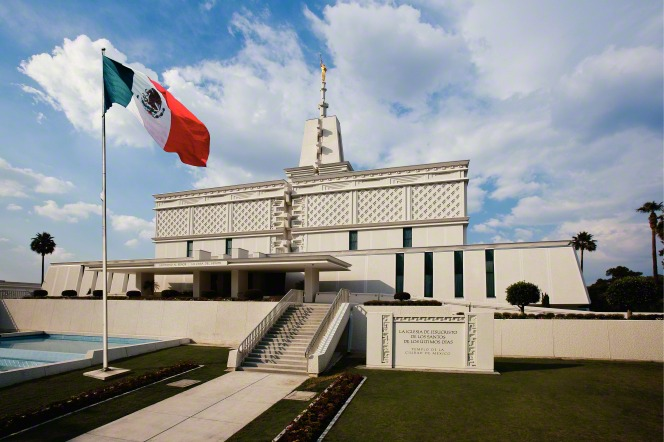 The front entrance of the Mexico City Mexico Temple is shown with the fountain, flag, and name sign in the surrounding landscape.