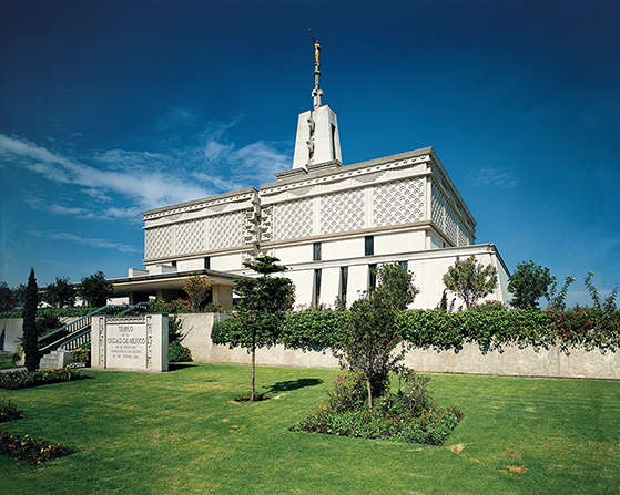 The Mexico City Mexico Temple viewed from the front entrance, with the name sign and trees and flowers in the daytime.