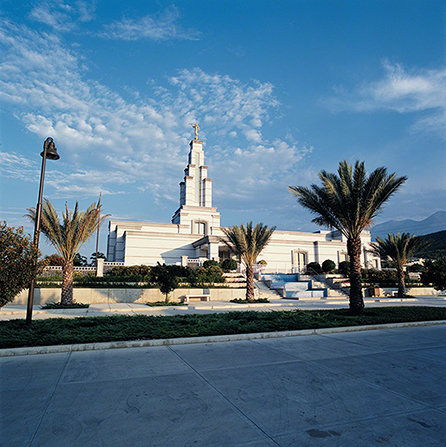 The Monterrey Mexico Temple is viewed from afar, with its landscape of palm trees and plants that line the entrance.