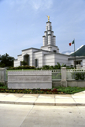 The name sign of the Monterrey Mexico Temple, with the Mexican flag waving in the wind.