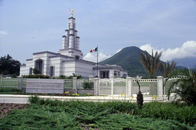 The Monterrey Mexico Temple on a sunny day, with green plants, trees, yellow flowers, the entrance gate and fences, the name sign in front, and a mountain seen in the distance.