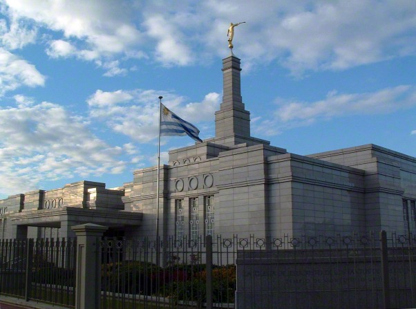 A side view of the entrance to the Montevideo Uruguay Temple, with the Uruguayan flag, in the evening.