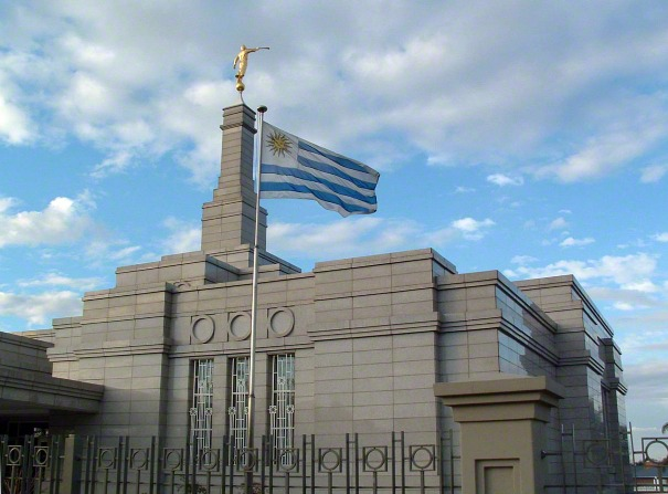 The Uruguayan flag by the front entrance to the Montevideo Uruguay Temple, blowing in the wind in front of the spire and angel Moroni.