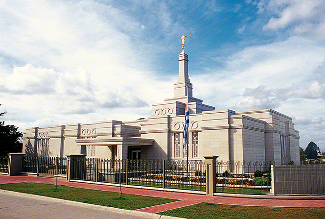 The sun lights up the flag, fences, and exterior of the Montevideo Uruguay Temple.