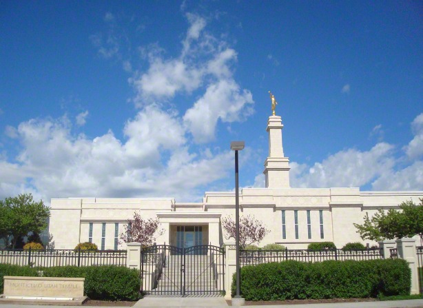 The front entrance to the Monticello Utah Temple on a sunny day, including the name sign and entrance gate, with blue skies and white clouds.