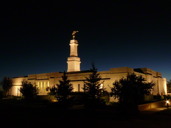 A night view of the Monticello Utah Temple lit up, with silhouetted trees in front.