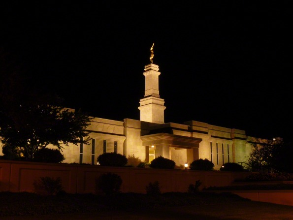 The front entrance side of the Monticello Utah Temple lit up at nighttime, with scenery of bushes and trees and with the angel Moroni atop the spire.